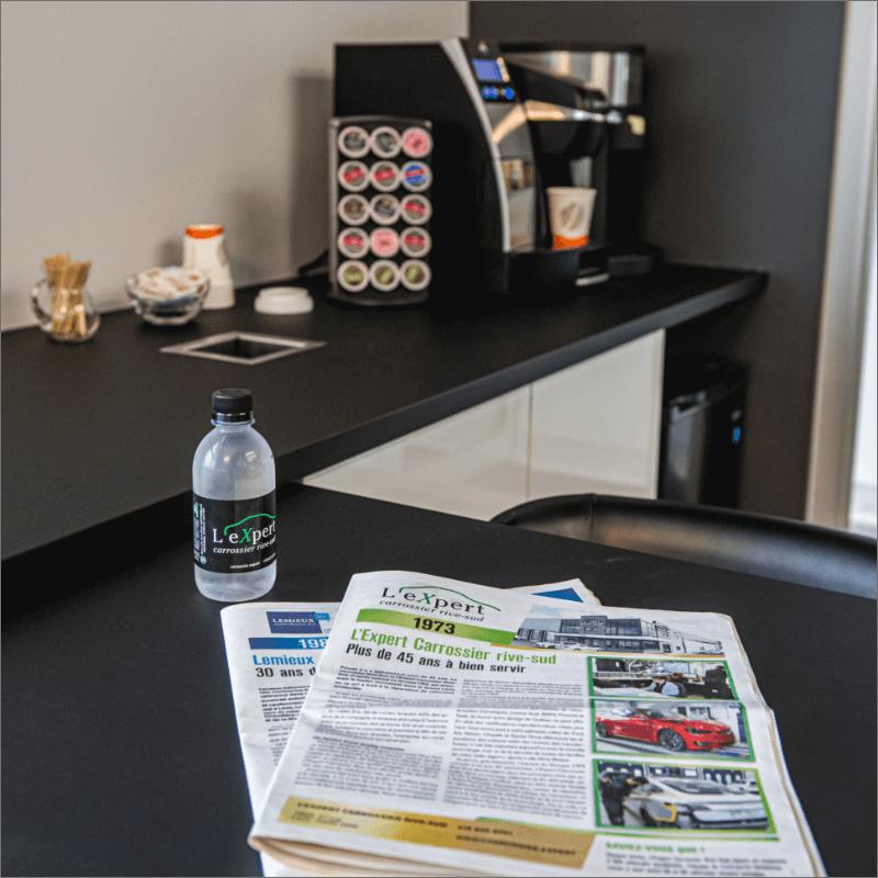 L'Expert Carrossier - Machine à cafés de la salle d'attente avec bouteille d'eau et journaux