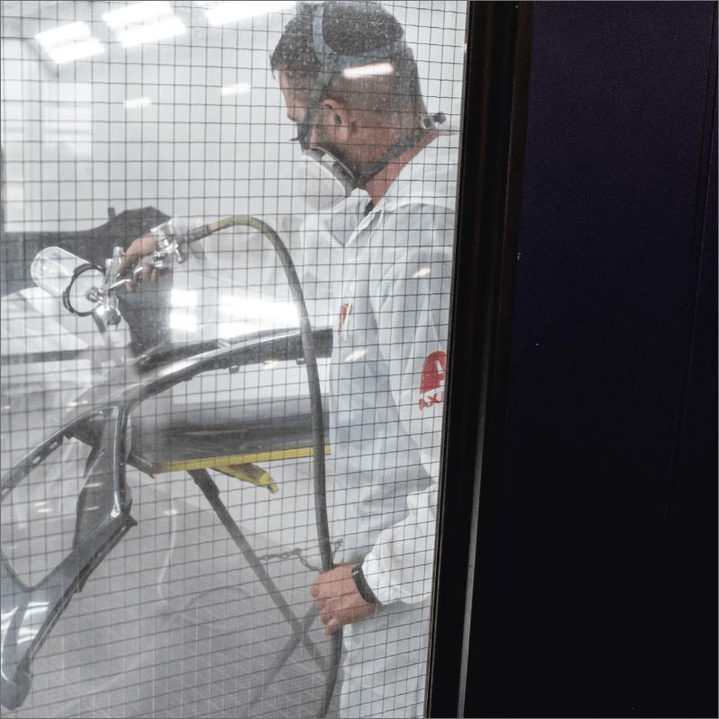 L'Expert Carrossier - Membre de l'équipe en train d'appliquer de la peinture avec le pistolet à peinture