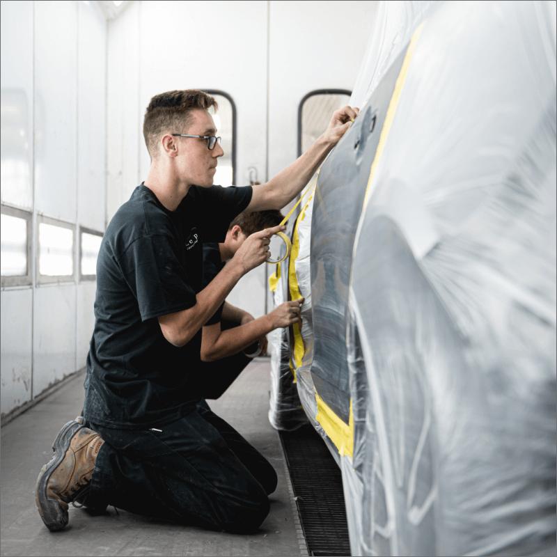 L'Expert Carrossier - Équipe dans la chambre à peinture en train de recouvrir un véhicule noir