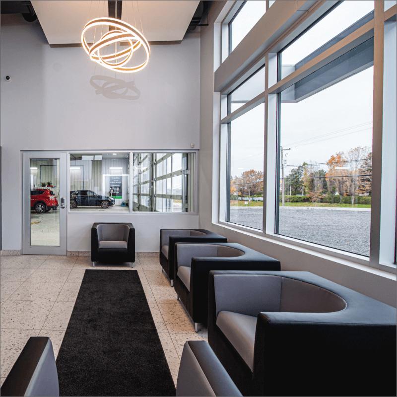 L'Expert Carrossier - Salle d'attente avec fauteuils et vue sur le garage intérieur